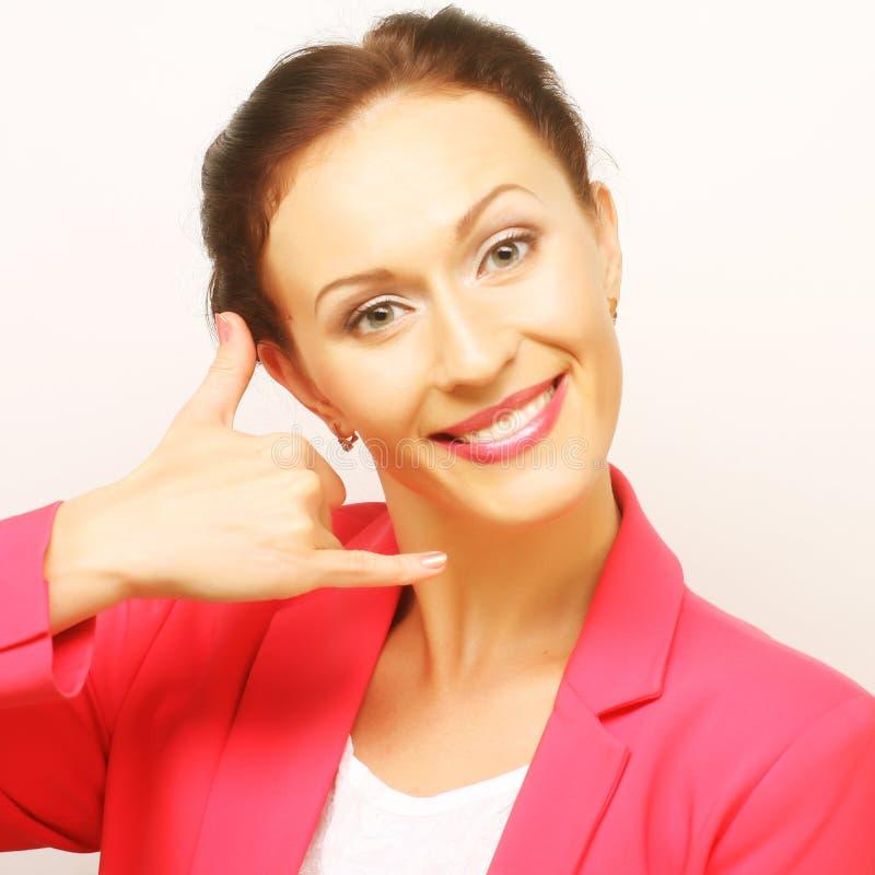 Affärskvinna som efterapar en påringning genom att använda handen royaltyfri foto
