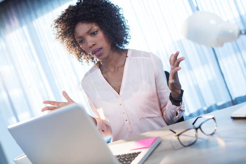 Affärskvinna som får ilsken på datoren royaltyfri bild