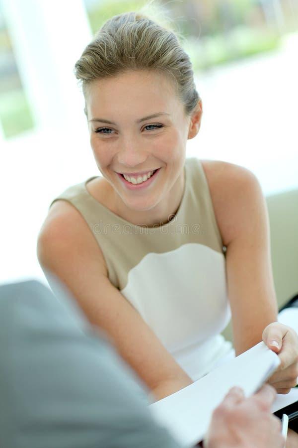 Affärskvinna som förhandlar avtalet och att le arkivbild