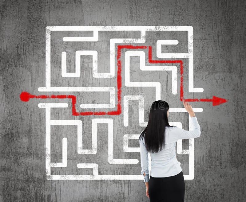 Affärskvinna som finner lösningen av en labyrint arkivbild
