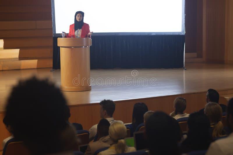 Affärskvinna som framme ger anförande av åhörare i salongen arkivbild