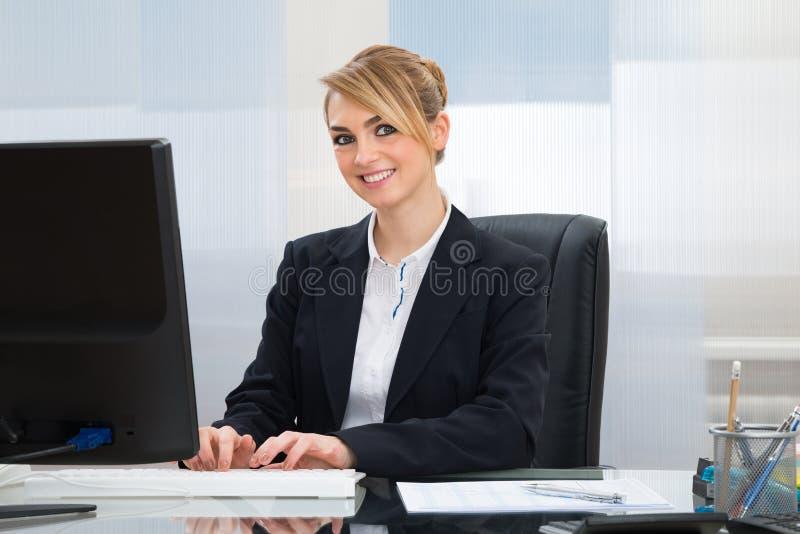 Affärskvinna som fungerar på datoren royaltyfri bild