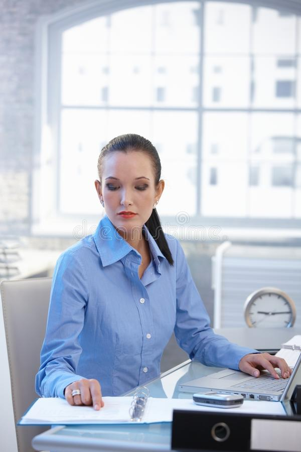 Affärskvinna som fungerar på skrivbordet royaltyfria bilder