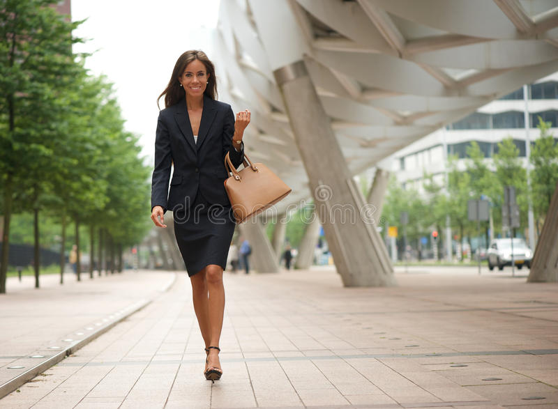 Affärskvinna som går i staden med handväskan royaltyfri fotografi
