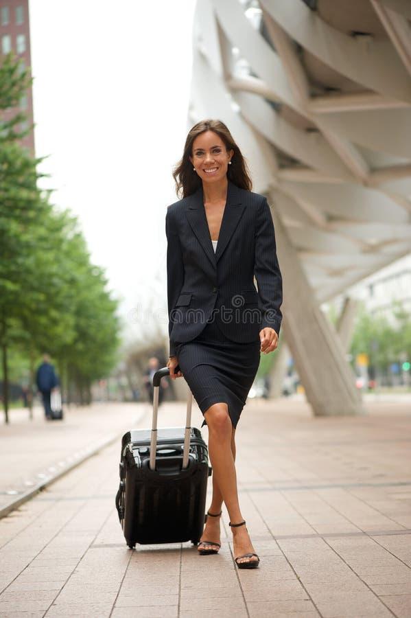 Affärskvinna som går i staden med resväskan fotografering för bildbyråer