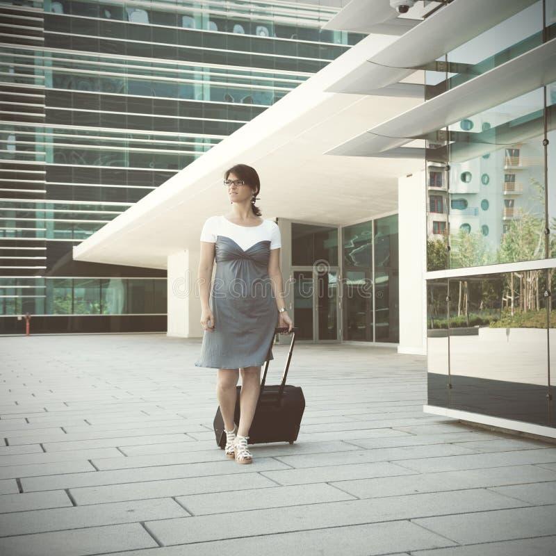 Affärskvinna som går med hennes bagage fotografering för bildbyråer