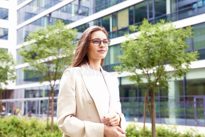 Affärskvinna som går på gatan mellan kontorsbyggnader royaltyfri bild