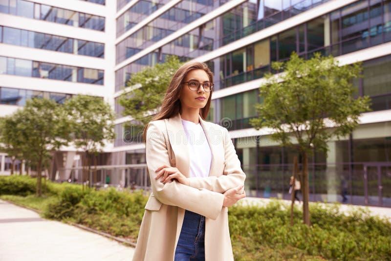 Affärskvinna som går på gatan mellan kontorsbyggnader royaltyfri fotografi