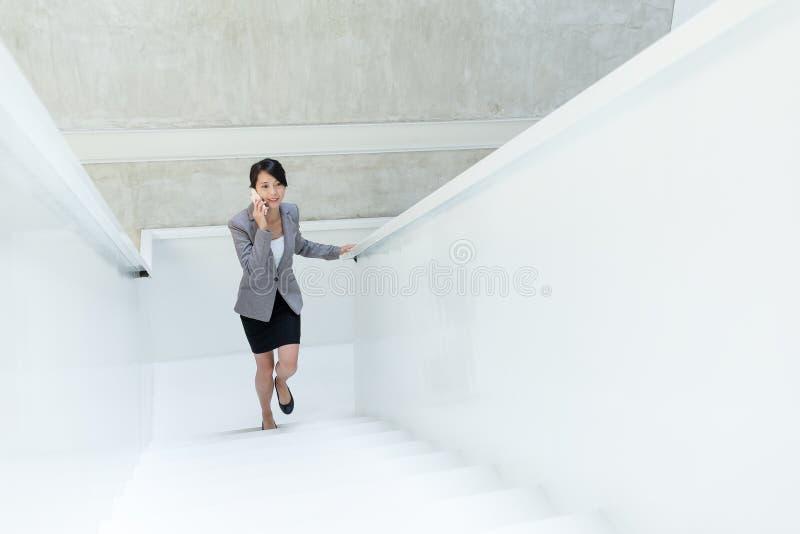 Affärskvinna som går upp trappa och samtal till mobiltelefonen fotografering för bildbyråer