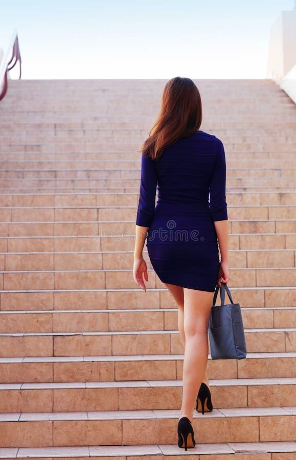 Affärskvinna som går upp trappan royaltyfria bilder