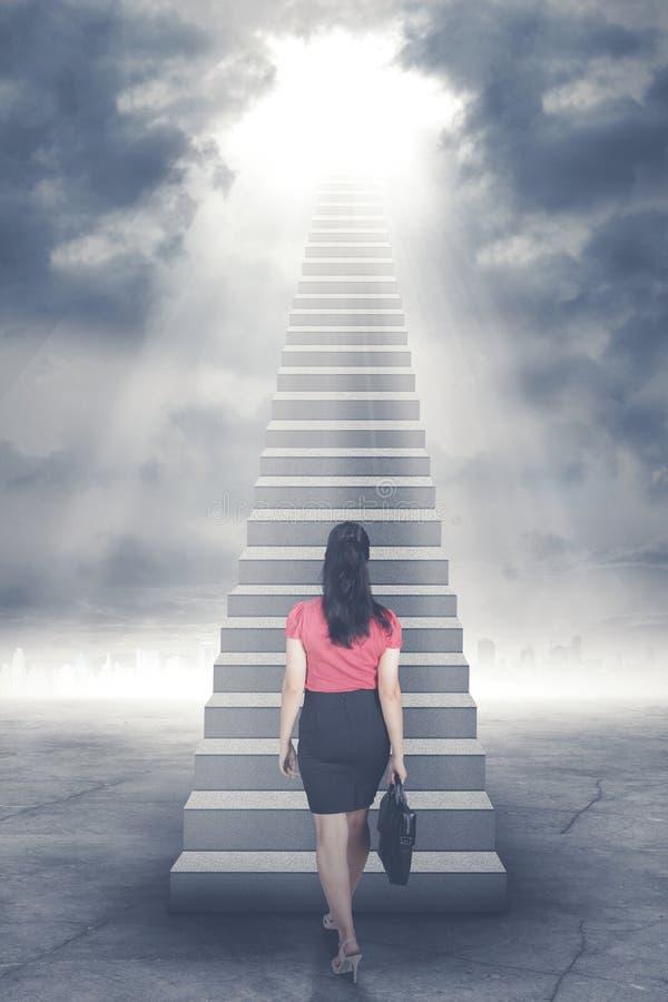 Affärskvinna som går upp trappuppgång till dörren i himmel med ljust ljust skina ner royaltyfri foto