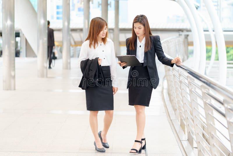 Affärskvinna som går utanför kontor och till varandra talar arkivfoton