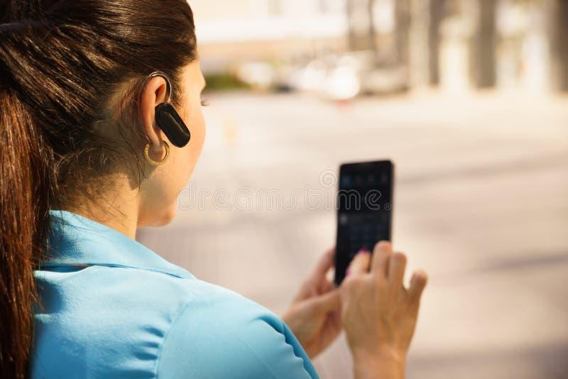 Affärskvinna som gör en påringning med bluetoothapparaten royaltyfri fotografi
