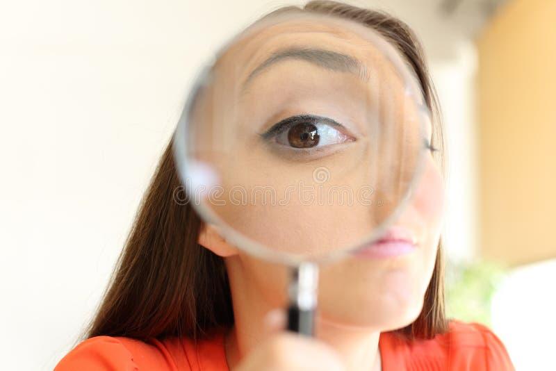 Affärskvinna som håller ögonen på dig med förstoringsapparatexponeringsglas arkivbild
