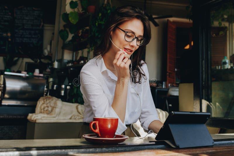 Affärskvinna som har en video pratstund på den digitala minnestavlan, medan sitta på coffee shop Kvinnligt sitta på fönstertabell arkivfoto