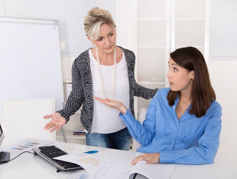 Affärskvinna som har problem på arbete: trakassera och att mobba, heras arkivfoton