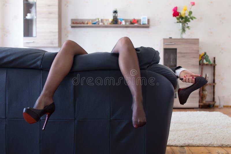Affärskvinna som hemma hänger sexiga långa ben på soffan efter workd fotografering för bildbyråer