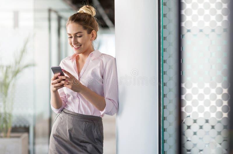 Affärskvinna som i regeringsställning använder smartphonen royaltyfria foton