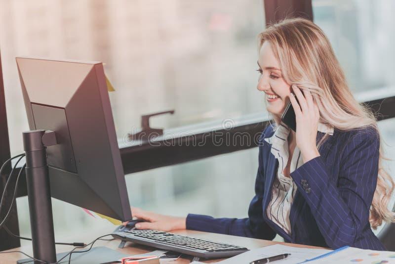 Aff?rskvinna som i regeringsst?llning arbetar med aff?rsp?ringning, medan genom att anv?nda datoren p? kontorsskrivbordet arkivbild