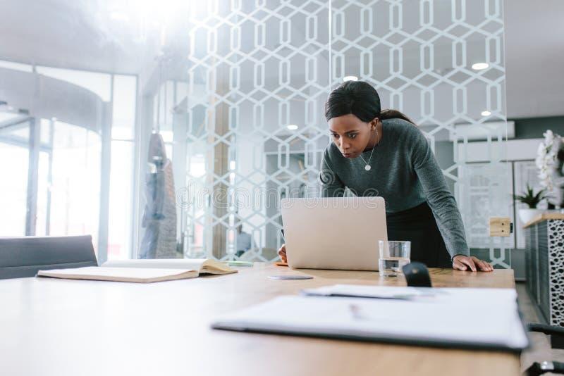 Affärskvinna som i regeringsställning arbetar på styrelse för bärbar dator arkivbild
