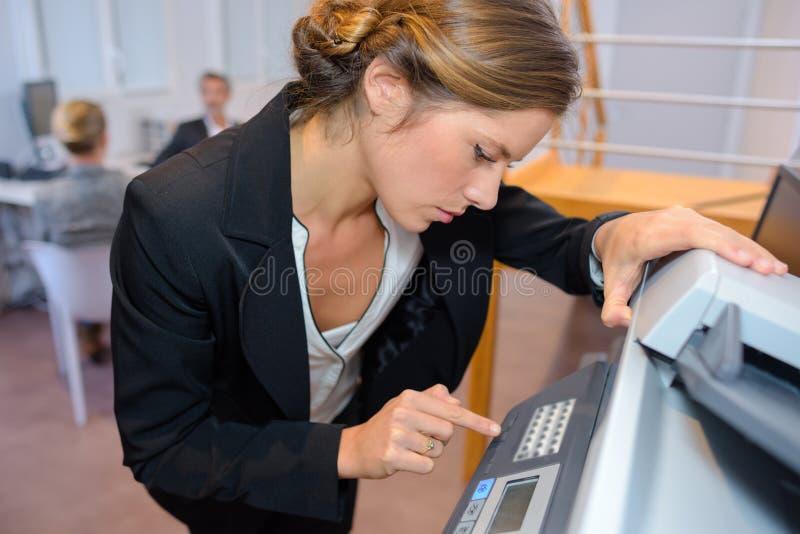 Affärskvinna som i regeringsställning fotokopierar dokument arkivbild