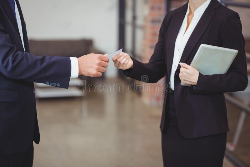 Affärskvinna som i regeringsställning ger affärskortet till klienten royaltyfri bild