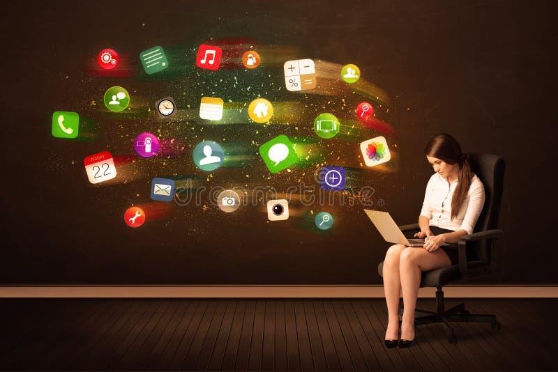 Affärskvinna som i regeringsställning sitter stol med bärbara datorn, och färgrikt royaltyfri fotografi