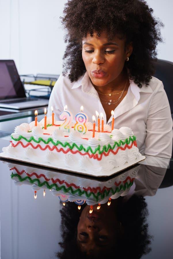 Affärskvinna som i regeringsställning som firar födelsedagpartiet blåser Cand royaltyfria foton