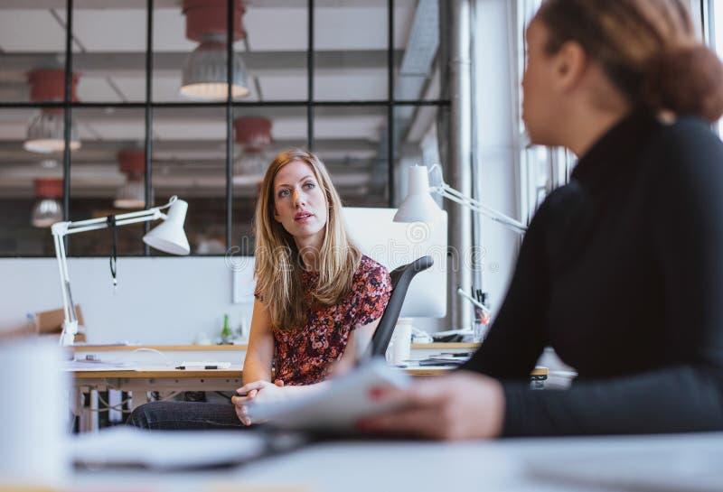 Affärskvinna som i regeringsställning talar med hennes kollega arkivfoto