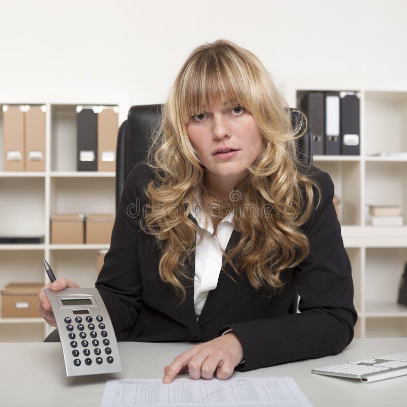 Affärskvinna som ifrågasätter en rapport arkivbilder