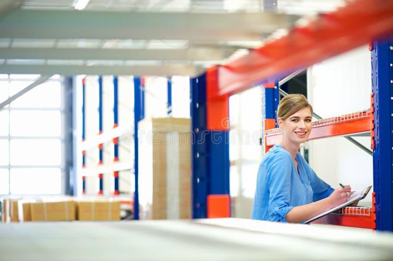 Affärskvinna som kontrollerar inventarium i ett lager arkivfoton