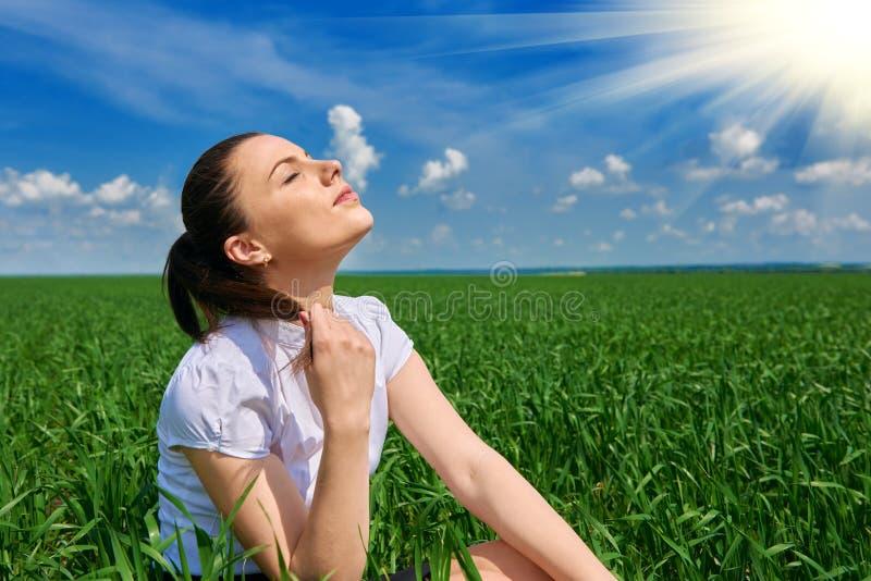 Affärskvinna som kopplar av i sol för fält för grönt gräs utomhus- under- Iklädd dräkt för härlig ung flicka som vilar, vårlandsk fotografering för bildbyråer