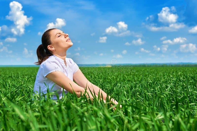 Affärskvinna som kopplar av i sol för fält för grönt gräs utomhus- under- Iklädd dräkt för härlig ung flicka som vilar, vårlandsk arkivfoto