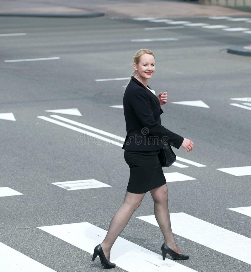 Affärskvinna som korsar gatan i staden royaltyfri fotografi