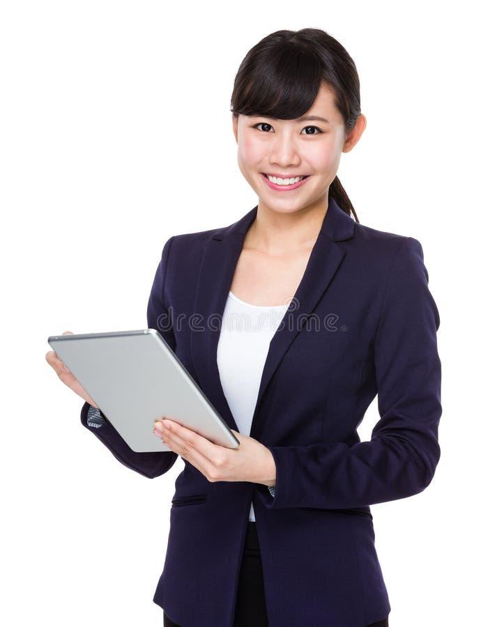 Affärskvinna som ler genom att använda minnestavlaPC arkivbilder
