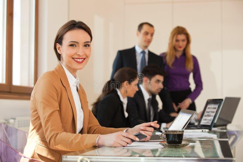 Affärskvinna som ler med kollegor i bakgrund fotografering för bildbyråer