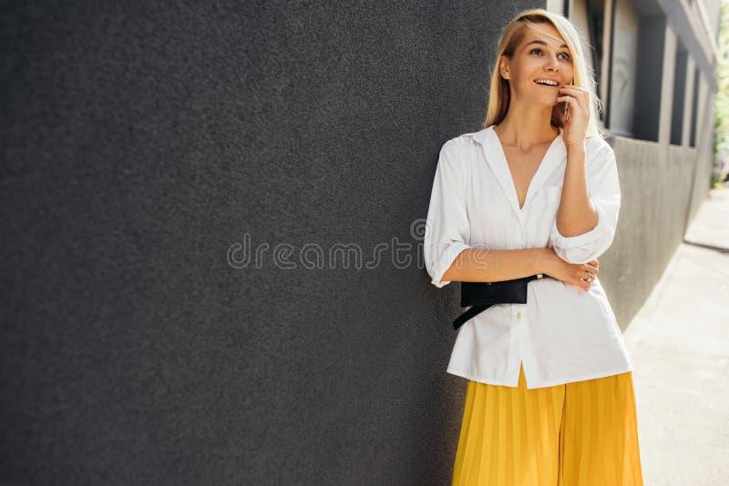 Affärskvinna som ler och står mot grå byggnads vägg, medan tala på den smarta telefonen Den härliga studentkvinnlign klädde I arkivfoto