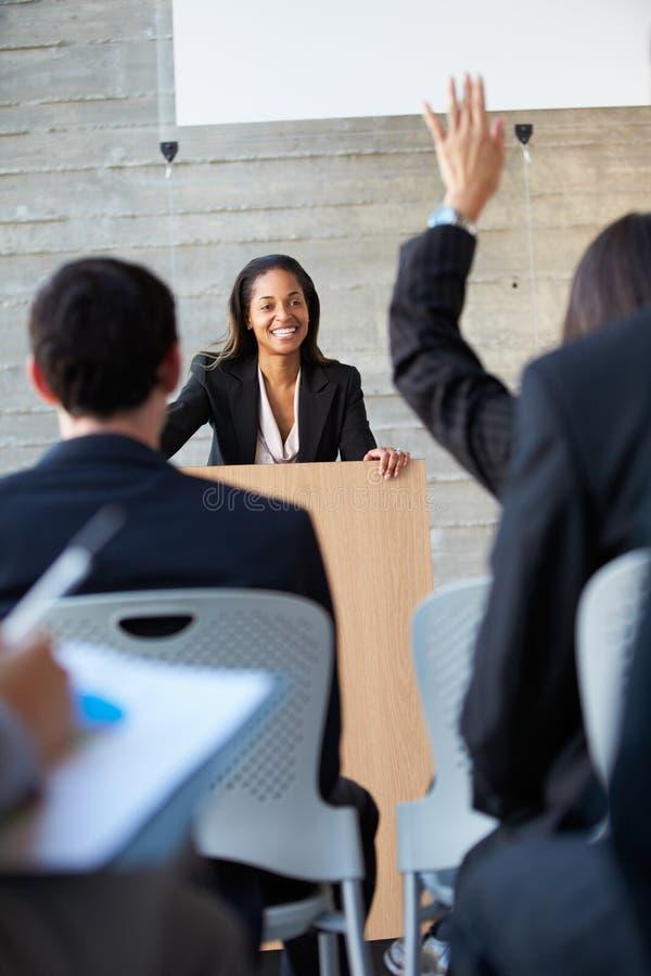 Affärskvinna som levererar presentation på konferensen arkivfoto