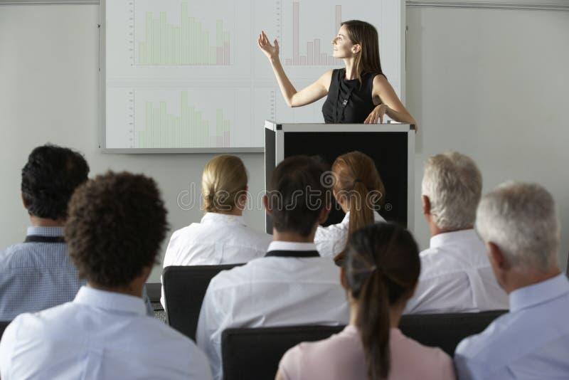 Affärskvinna som levererar presentation på konferensen royaltyfri foto