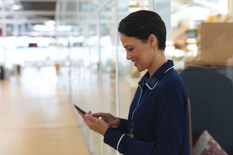 Affärskvinna som lutar på G; rövvägg och användamobiltelefon i ett modernt kontor arkivfoton