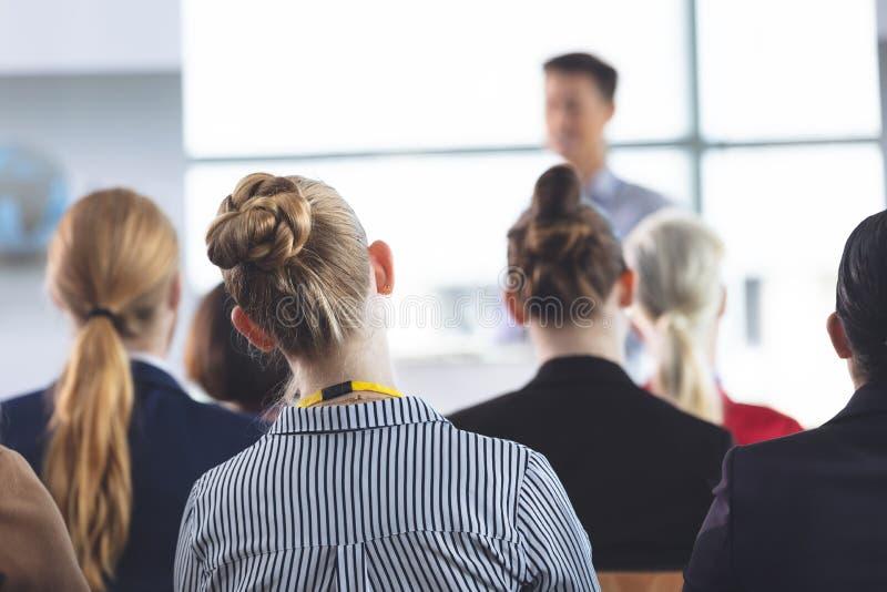 Affärskvinna som lyssnar till anförande på ett affärsseminarium arkivbild