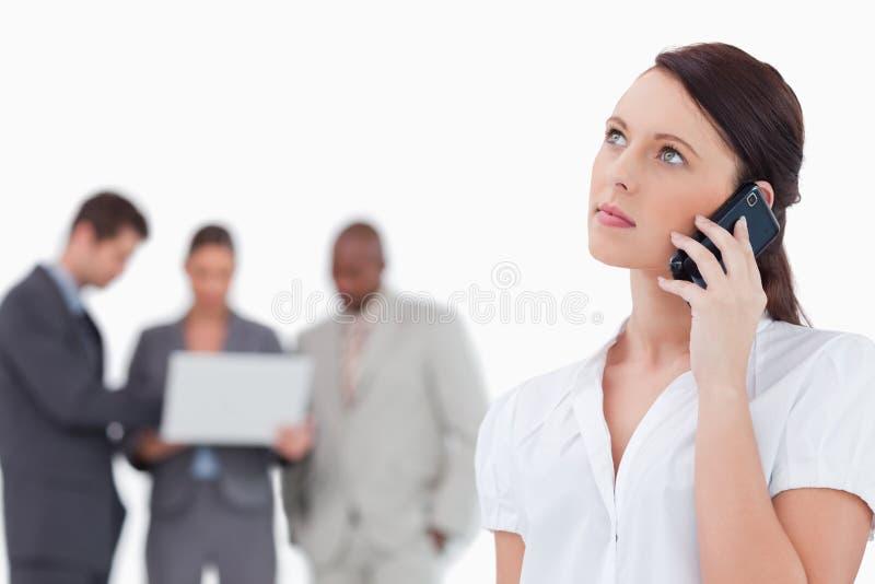 Affärskvinna som lyssnar till calleren med kollegor bak henne royaltyfri foto