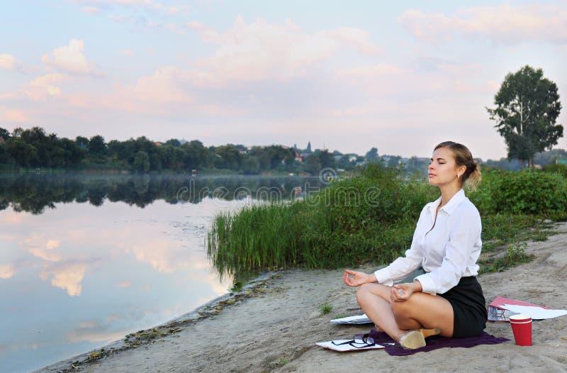 Affärskvinna som mediterar på kusten arkivbild