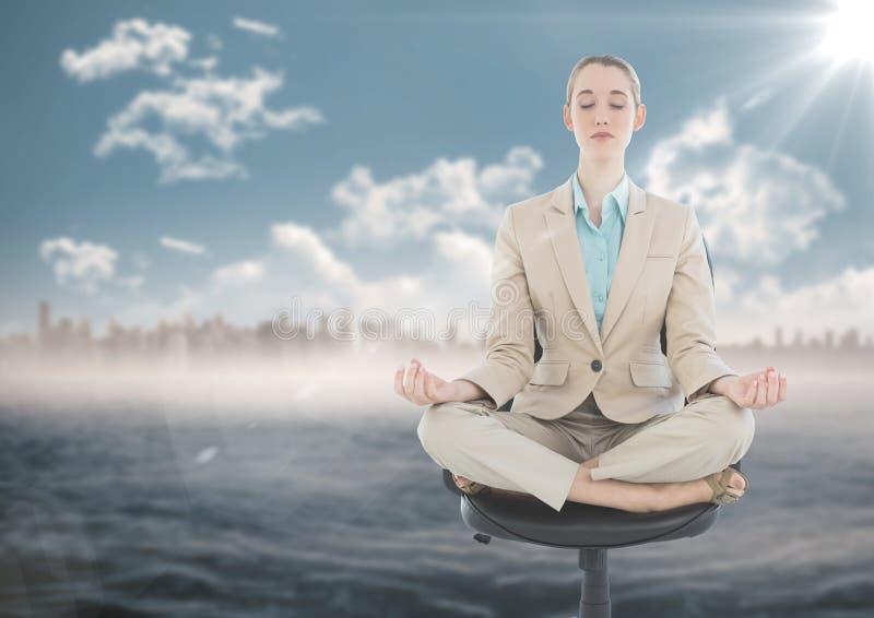 Affärskvinna som mediterar på stol mot vatten, och oskarp horisont med signalljuset fotografering för bildbyråer