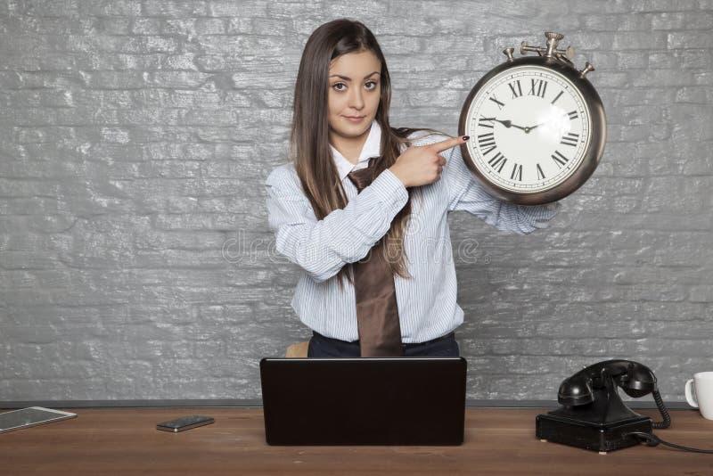 Affärskvinna som pekar på klockan, påminnelse för eftersläntrare arkivfoto