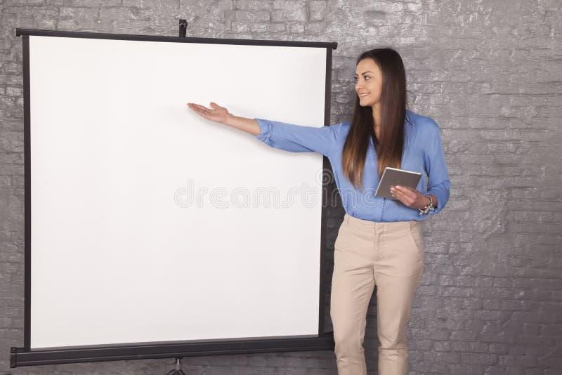 Affärskvinna som pekar till ett ställe på brädet, kopieringsutrymme arkivbilder