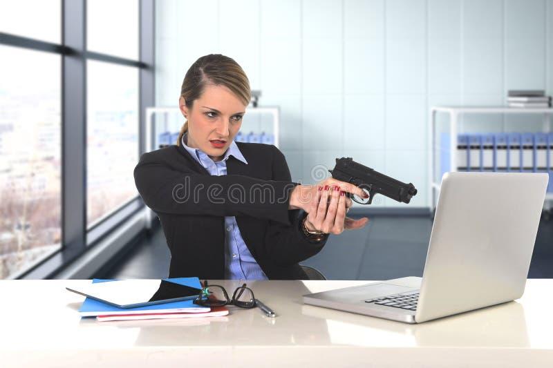 Affärskvinna som pekar vapnet till datorbärbar datorsammanträde på det stressat skrivbordet som är desperat och royaltyfria foton