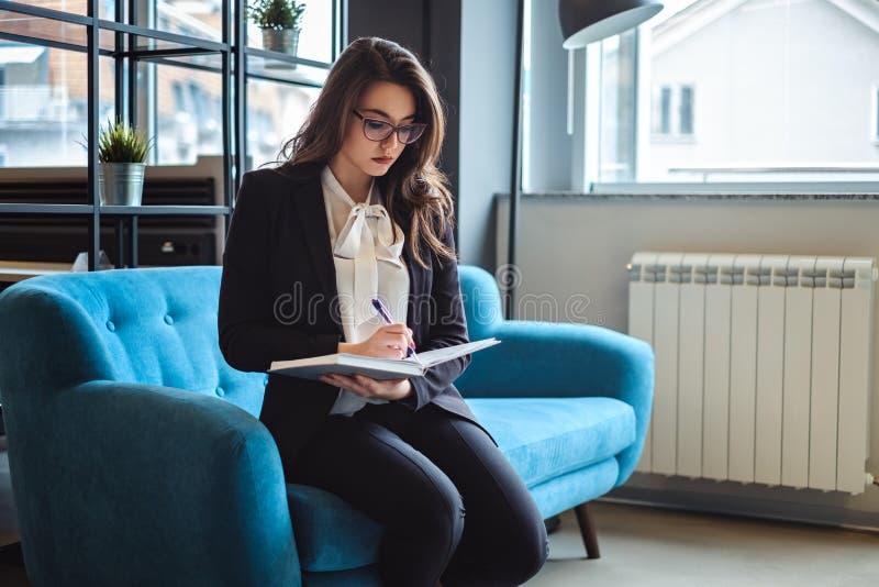 Affärskvinna som placerar i kontoret som vilar område och att skriva royaltyfria bilder