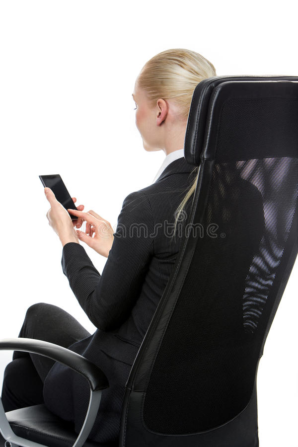 Affärskvinna som placeras på en stol arkivbild