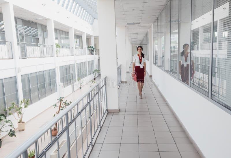 Affärskvinna som promenerar kontorskorridoren Le bakgrund för affärskvinnaGoes Against White kontor En ung nätt flicka arkivfoton